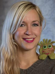 """Greenwood's Toni Carr, who goes by the nickname Joan of Dark, poses with an alien pet made of Peruvian highland wool at Vino Villa. Her new book, """"Geek Knits,"""" is her third on knitting."""