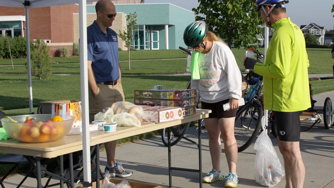 Lori Mayle and Guy Mendt stopped Wednesday to check out the food offered at the Windsor Recreation Center for Bike to Work Day. Sponsoring the food was Big City Burrito, Mr. Yo's Doughnuts, Gibbs Bagels and Senior Jalapeno's.