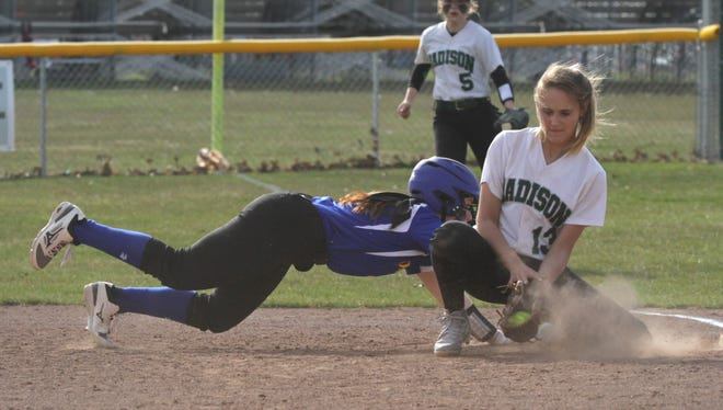 Ontario's Addi Kissinger dives back to first base in front of Madison's Paige Eldridge during a home game on Thursday.