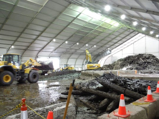 In a covered facility, dredged material is drained and sorted. Polluted water is cleaned with a wastewater treatment system.