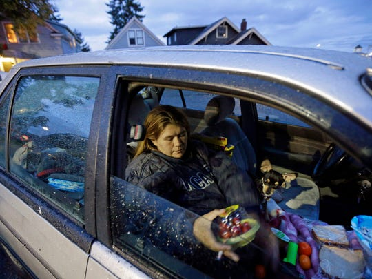 Paige Clem sits in the car she lives in along with her husband and three dogs outside a church where free food was being distributed in Everett. Clem, who said she has battled drug addiction in the past but was now clean, said having enough money just to run the heat in her car and move it when required, was a daily challenge.