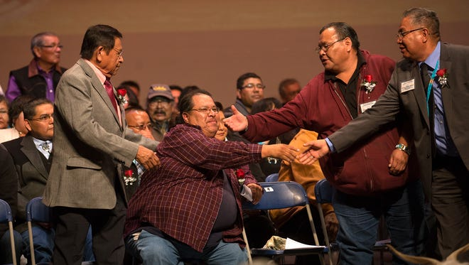 At center, Tsé Alnaozt'i'í Chapter President Frank Smith is congratulated by colleagues on Friday at the conclusion of the Navajo Nation's Northern Agency inauguration ceremony at the Phil L. Thomas Performing Arts Center in Shiprock.