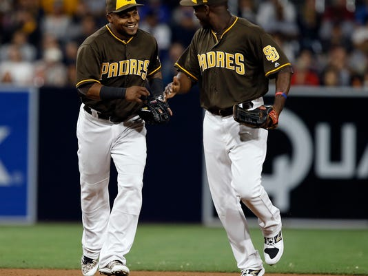 San Diego Padres shortstop Erick Aybar, left, gets congratulations from left fielder Jose Pirela for throwing out Detroit Tigers' Miguel Cabrera on a ground ball during the eighth inning of a baseball game in San Diego, Friday, June 23, 2017. (AP Photo/Alex Gallardo)