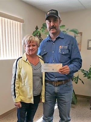 Nell Crimmins of White Sands Construction Inc. hands a check to Orlando Martinez of New Mexico Gas Company, to help pay the utility bill for one of Alamogordo's community member in need. This is the 10th year that White Sands Construction Inc. together with NM Gas Company has been making these types of donations.