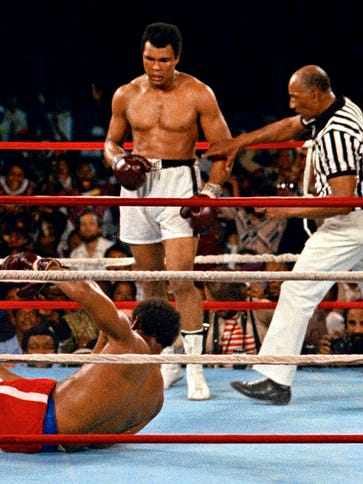 Referee Zack Clayton, right, steps in after Muhammad