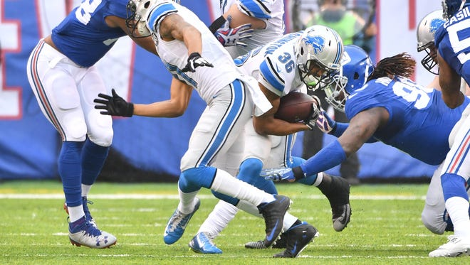 Lions running back Dwayne Washington looks for a hole in the Giants' line but finds none, being brought down by Damon Harrison in the first quarter.