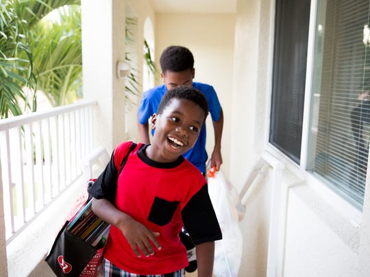 Sincere Forges, 7, and his older brother Izaiah, 14, carry in donated belongings for the new babies room at the Bridgewater Bay Apartments Thursday, May 11, 2017 in Naples. Jude Forges, along with her sons Izaiah, 14, and Sincere, 7, lost their home Monday, April 10th, 2017 in a fire at Bear Creek Apartments in North Naples.