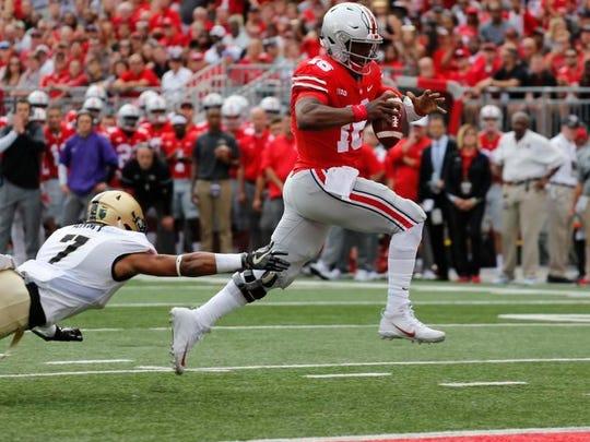 Ohio State quarterback J.T. Barrett, right, scores
