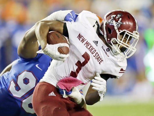 New Mexico State running back Larry Rose III (3) gains yardage before he is brought down by Florida defensive lineman Cece Jefferson, left, during the first half of an NCAA college football game, Saturday, Sept. 5, 2015, in Gainesville, Fla. (AP Photo/John Raoux)