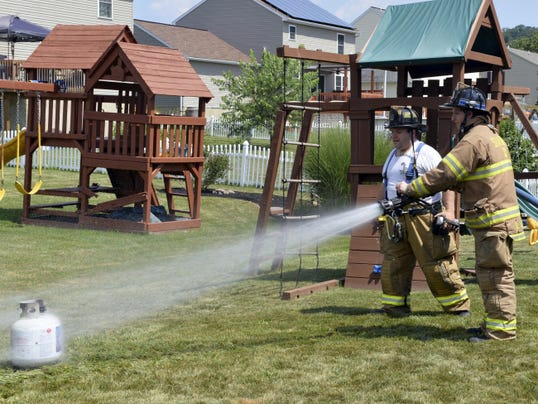 Jonestown Perseverance firefighter Dan Mohn watches as Adam Riddle hoses off a leaky, singed propane tank, the source of a grill fire at 125 Creek View Drive on Saturday afternoon. There was no reported damage to the house, but the grill was a loss.