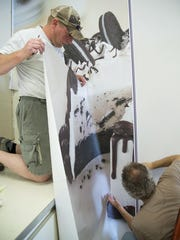 Workers Kip Gillin, left, and Erik Kalafat hang an Oreo cake vinyl wall covering for the newly renovated Baskin-Robbins store, set to reopen Wednesday at the same location at 2120 10th Ave S.