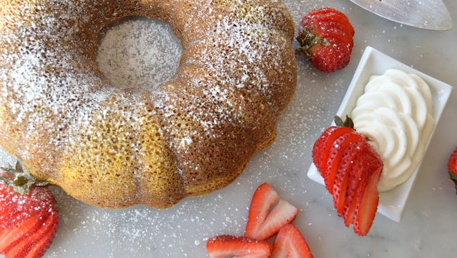 Olive Oil Rosemary Cornmeal Cake is served with berries and whipped cream.