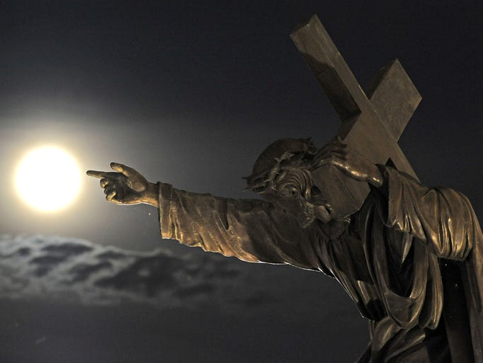 A supermoon rises above a Jesus Christ statue in front of the Holy Cross church  in Warsaw, Poland, Sunday, Aug. 10, 2014.