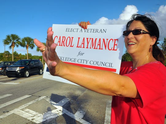 Carol Laymance held a campaign sign at the corner of Murrell Road and Barnes Boulevard about a week before the election.