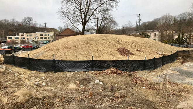 A mound on the site of the former 12 Bones restaurant building in the River Arts District is part of a temporary stream relocation to accommodate construction.
