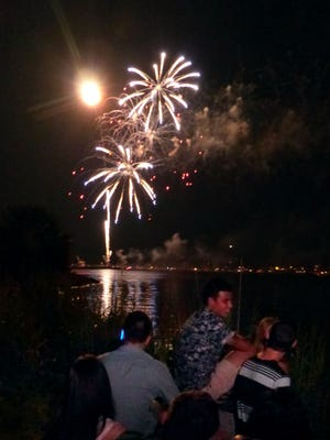 Spectators watch the Sertoma's 4th of July Downtown Pensacola fireworks display from the Bayfront Parkway Friday night.