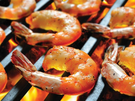 Grilled shrimps,prawns sizzle on the flaming grill.