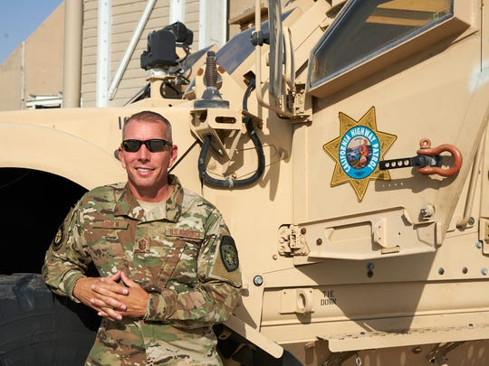 Dane Norem poses with a military vehicle during a recent deployment to the Middle East with the California Air National Guard.