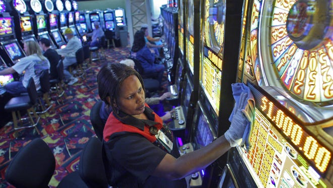 Ninday Veng of Des Moines cleans a slot machine at Prairie Meadows Racetrack and Casino in a 1999 photo. The authors say casino employees face higher risks for secondhand-smoke related illness than other workers.