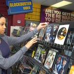 Destiny Thomas, clerk at the Blockbuster Video in Opelousas, sorts a shelf of DVDs on display at the last store with its name in the entire state.