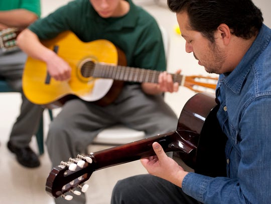 Carlos Rodriguez of Mezcal teaches guitar to youth