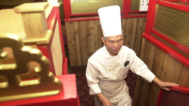 Master chef and owner Kam Sang Kwan visits with guests at his restaurant in 2004.