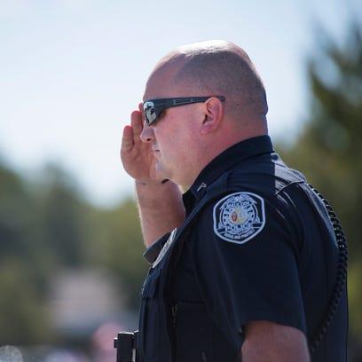A Mauldin police officer salutes as Milton Reece Surratt,