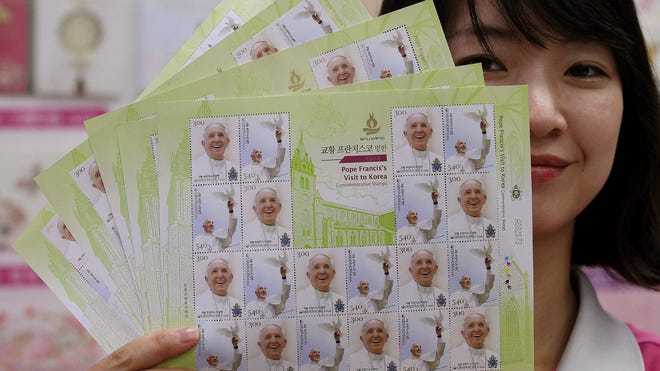 A worker at the Gwanghwamun Post Office unveils sheets of stamps to commemorate Pope Francis' visit to South Korea in Seoul, South Korea, Thursday, Aug. 7, 2014. Pope Francis is scheduled to make a five-day trip to South Korea, starting Aug. 14 to participate in a Catholic youth festival and to preside over a beatification ceremony for 124 Korean martyrs.