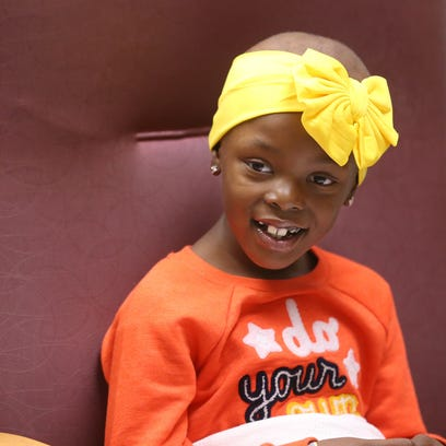 Jenesis Shaw, 8, flashes a smile during her treatment