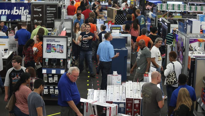 People look at merchandise while holiday shopping at Best Buy on Thanksgiving day, Thursday, Nov. 26, 2015, in Panama City, Fla. (Patti Blake/News Herald via AP)