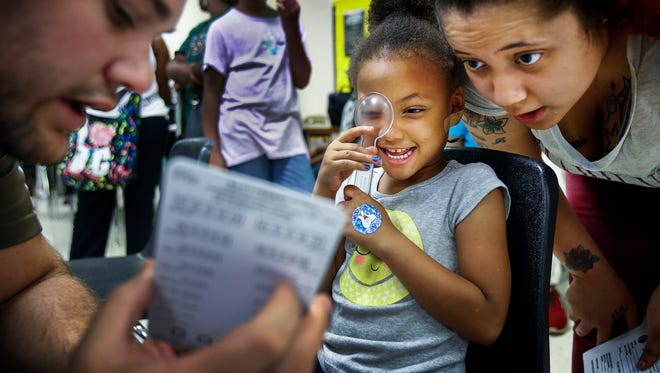 Evette Fleming, 4, with help from mother Dianecia Fleming, receives a free eye exam during an annual Back to School Health Fair and Family Festival at Whitehaven High School.