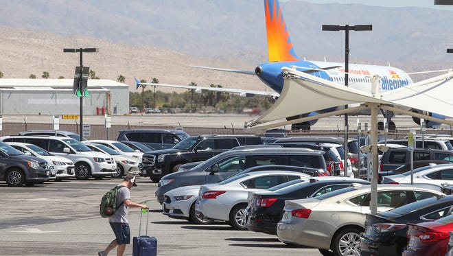 A traveller makes his way through a lot of rental cars at the Palm Springs International Airport, April 12, 2017.
