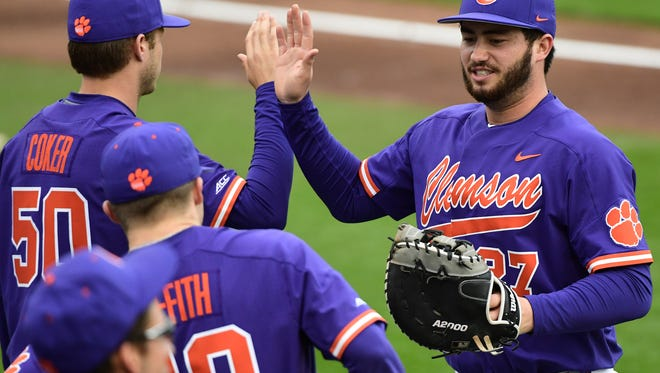 Clemson senior infielder Chris Williams(27), right, is greeted by teammates after getting out of the during the top of the second inning against William and Mary on Saturday at Doug Kingsmore Stadium in Clemson.