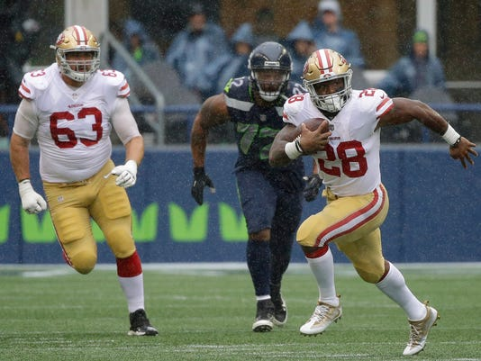 San Francisco 49ers running back Carlos Hyde (28) runs ahead of Seattle Seahawks defensive end Michael Bennett (72) as offensive guard Brandon Fusco (63) looks on in the first half of an NFL football game, Sunday, Sept. 17, 2017, in Seattle. (AP Photo/Elaine Thompson)