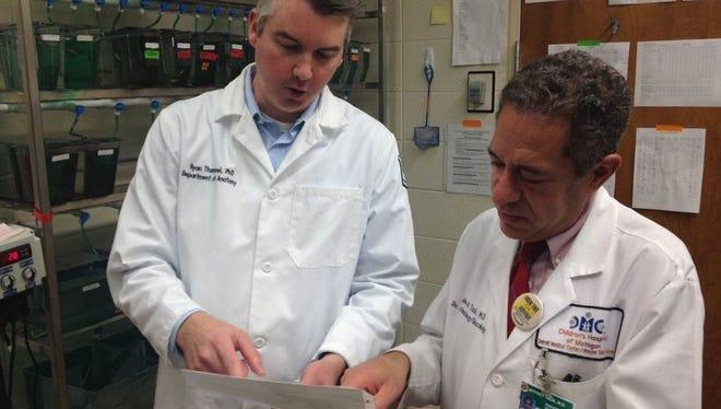 Wayne State University developmental geneticist Ryan Thummel and Dr. Jeffrey Taub chief of Oncology at Children's Hospital of Michigan  talk in a Wayne State zebrafish lab