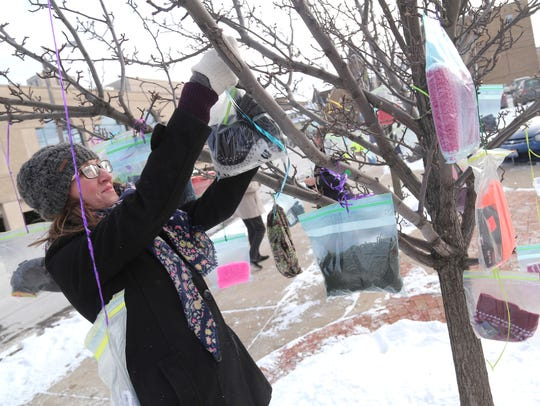 Emily Volz hangs hats and mittens on branches at Third