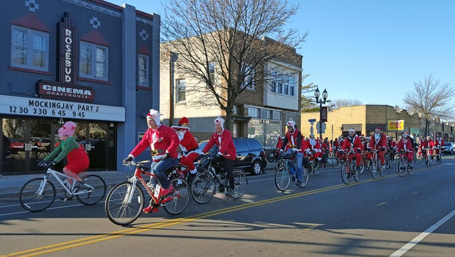 Cyclists make their way east along North Ave. from the start of the Santa Cycle Rampage at Cranky Al's in Wauwatosa on Dec. 5, 2015.