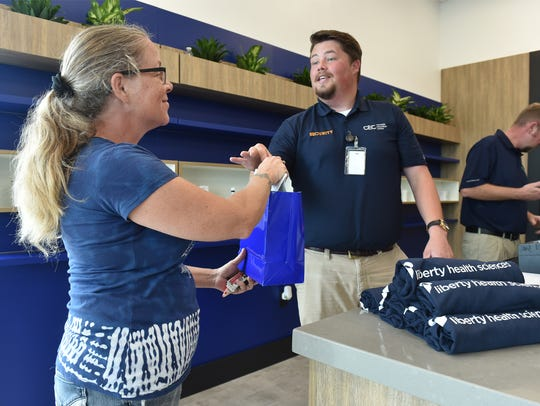 Cindy Aliberti, of Jensen Beach, receives her products from Tanner Culbreth after making the first purchase at the Liberty Health Sciences Cannabis Education Center, the first medical cannabis dispensary in Port St. Lucie, on Friday, June 1, 2018, at 10491 South US Highway 1 in Port St. Lucie.