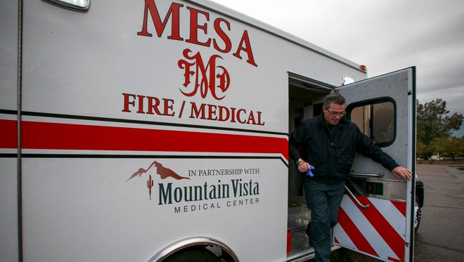 A nurse practitioner is shown exiting a Mesa Fire and Medical vehicle.