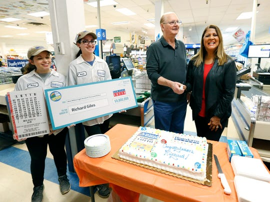 Richard Giles, 76, of Macedon gets ready to cut a cake with lottery spokeswoman Yolanda Vega at Hegedorns Market in Webster. He will receive $4,419,643 after the required withholdings. Giles won the flagship Lotto game on Oct. 11, 2017 after purchasing several tickets at Hegedorns.