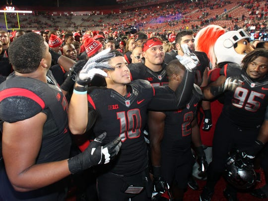 Rutgers quarterback Gary Nova conducts the playing of the alma mater surrounded by teammates after a win against Indiana.