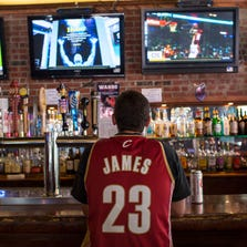 CLEVELAND, OH - JULY 11: A Cleveland Cavaliers fan wearing a Lebron James jersey watches news coverage of LeBron James return to Cleveland at Panini's Bar and Grille in downtown Cleveland on July 11, 2014 in Cleveland, Ohio (Photo by Angelo Merendino/Getty Images)