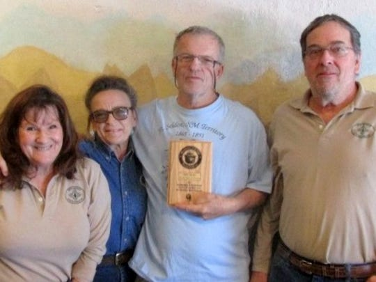 Mike Bilbo, third from left, holds a plaque from the staff at the Smokey Bear Historical. From left, they are Linda Wallace, Bennie-Long and Brady Park.