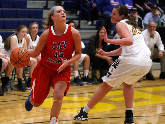 Jay County's Bre Mcintire dribbles the ball past Delta's