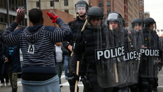 A protester holds up his hands as police in riot gear pass through during a march in honor of Freddie Gray on April 25, 2015, in Baltimore.