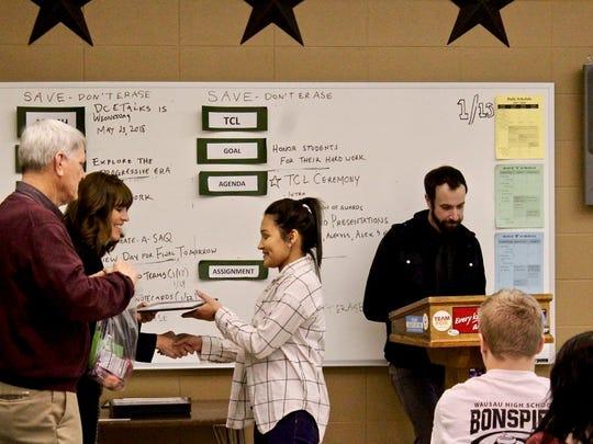 Kristine Gilmore and Paul Aleckson congratulate a Teachers