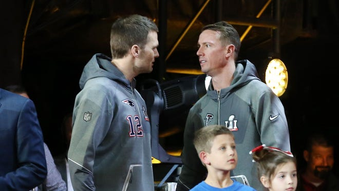 New England Patriots quarterback Tom Brady (left) talks with Atlanta Falcons quarterback Matt Ryan during Super Bowl LI Opening Night at Minute Maid Park.