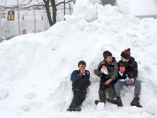 As heavy snow canceled school on a Tuesday last year Logan Sturgill, 11, his brother Hunter, 13, and their friend Sam Pugliese, sit on a pile of snow as they drink hot chocolate in Shrewsbury.