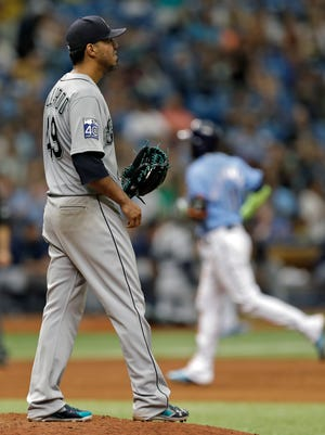 Seattle Mariners starting pitcher Yovani Gallardo watches as Tampa Bay Rays' Adeiny Hechavarria runs around the bases after Hechavarria hit a two-run home run during the seventh inning of a baseball game, Sunday, Aug. 20, 2017, in St. Petersburg, Fla. (AP Photo/Chris O'Meara)