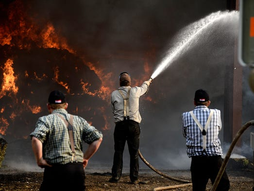 Members of the Big Stone Colony, near Sand Coulee, fight a hay fire in a barn on the colony on Wednesday evening.